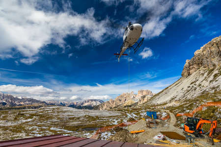 Helicopter used for rescue operations also for bringing construction materials, on the ground Tre Cime di Lavaredo in Dolomites, Italy.