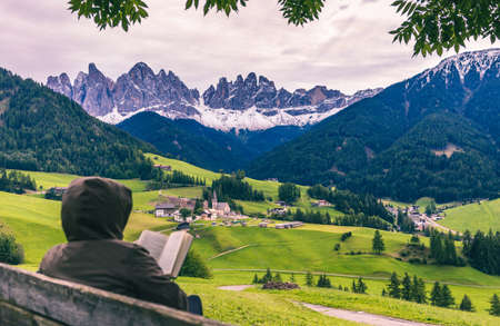 Tourist reading a book sitting on the wooden bench at autumn forest and mountains background, Santa Magdalena village, Dolomites, South Tyrol, Italy Stock Photo