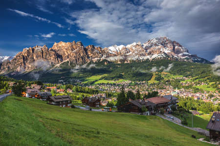 Cortina dAmpezzo town panoramic view with alpine green landscape and massive Dolomites Alps in the background. Province of Belluno, South Tyrol, Italy.