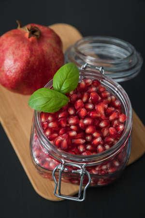 Ripe pomegranate fruit in a jar on wooden vintage background