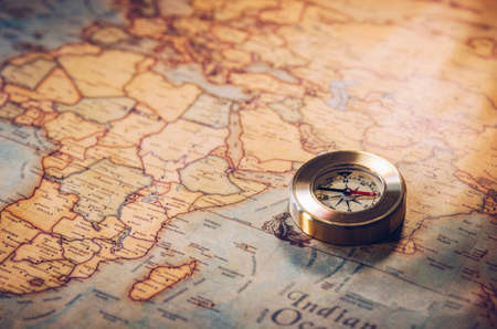 Old vintage retro golden compass on ancient map. Selective focus, shallow depth of field. Concept of world travel, sightseeing and tourism.
