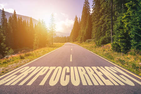 Cryptocurrency word written on road in the mountains