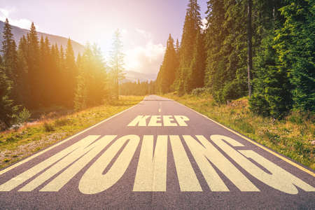 Blijf tekst verplaatsen die op de weg in de bergen is geschreven Stockfoto
