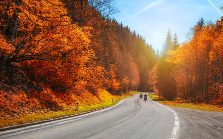 Bikers on mountainous highway, biker on the road in sunset light in autumn riding on curve road pass across Alpine mountains, extreme lifestyle, freedom concept. Austria, Alps