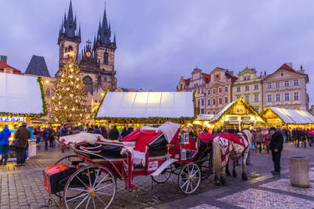 Prague Christmas market on the night in Old Town Square. Tyn Church, Bohemia. Blurred people on the move. Prague, Czech Republic. Reklamní fotografie