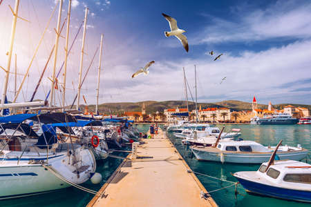 Yachts parking in harbor, Harbor in Trogir, Croatia. Sailboats reflected in water, water transport, beautiful vessel in the harbor, summer vacation, active lifestyle, holiday concept. Trogir, Croatia.