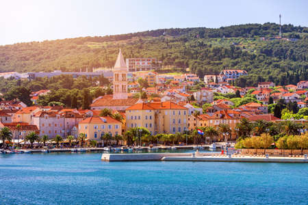 Supetar city in Brac island, Croatia. View from the sea. Picturesque scenic view on Supetar on Brac island, Croatia. Panoramic view on harbor of town Supetar from the side of sea. Brac, Croatia. Imagens