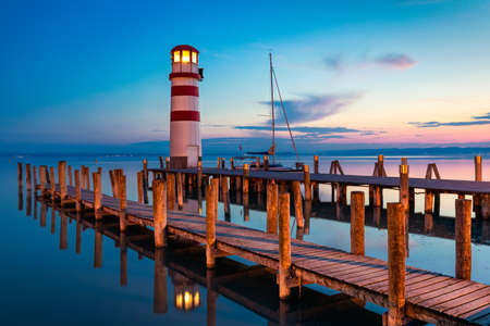 Lighthouse at Lake Neusiedl, Podersdorf am See, Burgenland, Austria. Lighthouse at sunset in Austria. Wooden pier with lighthouse in Podersdorf on lake Neusiedl in Austria. Standard-Bild