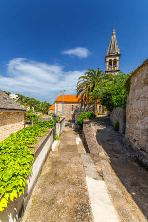 Church building and palm tree against sunny blue sky in Splitska village on Brac island, Croatia.