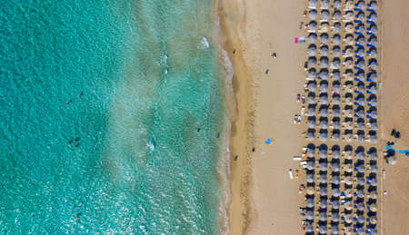 Top down aerial view of amazing beach with umbrellas and turquoise sea at sunset. Mediterranean sea, Crete, Greece. 免版税图像
