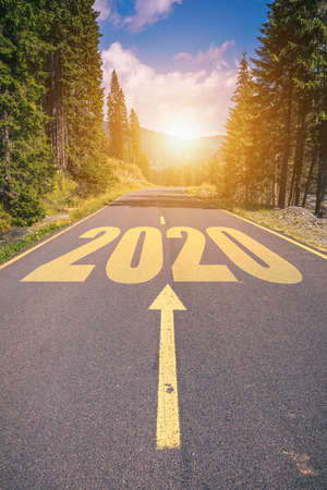 Empty asphalt road and New year 2020 concept. Driving on an empty road in the mountains to upcoming 2020 and leaving behind old 2019. Concept for success and passing time.