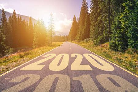 Carretera de asfalto vacía y concepto de año nuevo 2020. Conducir por una carretera vacía en las montañas hasta el próximo 2020 y dejar atrás el antiguo 2019. Concepto para el éxito y el paso del tiempo. Foto de archivo