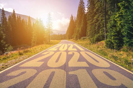 Empty asphalt road and New year 2019, 2020, 2021 concept. Driving on an empty road in the mountains to upcoming 2019, 2020, 2021 and leaving behind old years. Concept for success and passing time. Stock Photo