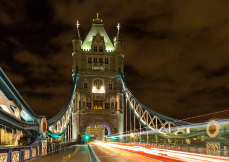 Tower Bridge in London, UK at night with moving red double-decker bus leaving light traces Stockfoto - 115398176