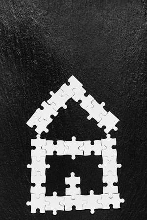 House made of puzzles. Modern house puzzle white pieces for concept design. Jigsaw Home, building, exterior. Puzzle construction renting, leasing, mortgage. House is made up of pieces of puzzles.