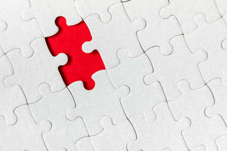 Unfinished white jigsaw puzzle pieces. Fill in pieces of the jigsaw puzzle. Complete the jigsaw puzzle with the missing pieces. Fragment of a folded white jigsaw puzzle. Standard-Bild - 121894816