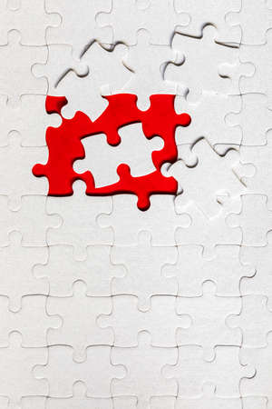 White jigsaw puzzle. White puzzle pieces on color background. Unfinished white jigsaw puzzle pieces on color background.