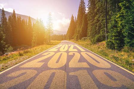 Leere Asphaltstraße und neues Jahr 2019, 2020, 2021 Konzept. Auf einer leeren Straße in den Bergen bis 2019, 2020, 2021 fahren und alte Jahre hinter sich lassen. Konzept für Erfolg und Zeitvertreib.