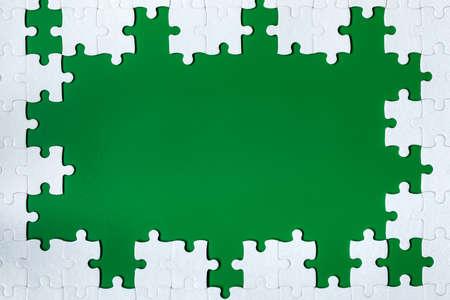 Encadrement en forme de rectangle, composé d'un puzzle blanc. Cadrez le texte et les puzzles. Cadre composé de pièces de puzzle sur fond vert. Banque d'images