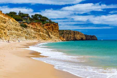 Praia de Porto de Mos in Lagos, Portugal. Praia do Porto de Mos, long beach in Lagos, Algarve region, Portugal. Beautiful golden beach, surrounded by impressive rock formations.