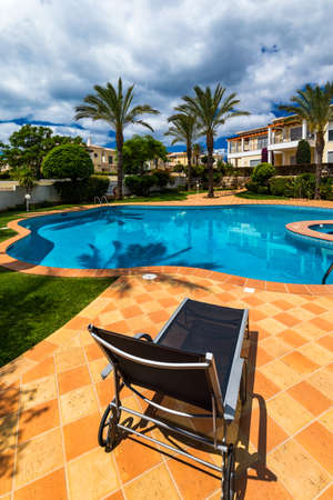 Great backyard with swimming pool, hot tub and lounge chairs. Swimming pool in backyard. Incredible swimming pool and garden with palm trees and flowers in a sunny day.