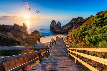 Camilo Beach (Praia do Camilo) an der Algarve, Portugal mit türkisfarbenem Meer im Hintergrund. Holzsteg zum Strand Praia do Camilo, Portugal. Herrlicher Blick auf Camilo Beach in Lagos, Algarve, Portugal. Standard-Bild