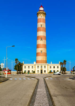 Lighthouse of Praia da Barra during the day, with a clear blue sky.