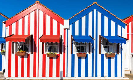 Street with colorful houses in Costa Nova, Aveiro, Portugal. Фото со стока