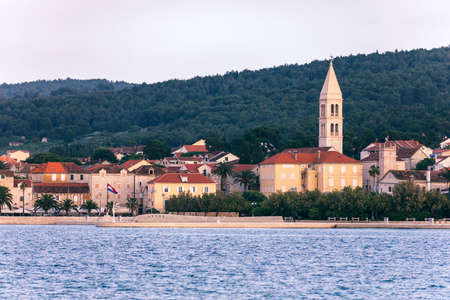 Supetar city in Brac island, Croatia. View from the sea. Picturesque scenic view on Supetar on Brac island, Croatia. Panoramic view on harbor of town Supetar from the side of sea. Brac, Croatia. 版權商用圖片