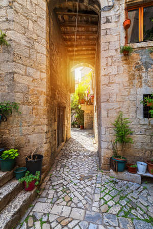 Narrow street in historic town Trogir, Croatia. Travel destination. Narrow old street in Trogir city, Croatia. The alleys of the old town of Trogir are very picturesque and full of charm. Croatia. Standard-Bild