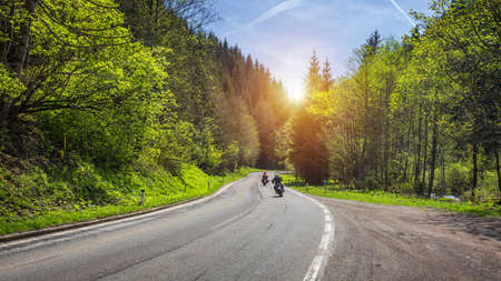 Bikers on mountainous highway, biker on the road in sunset light riding on curve road pass across Alpine mountains, extreme lifestyle, freedom concept. Austria, Alps