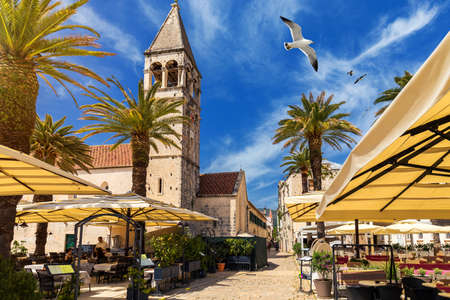 View at town Trogir, old touristic place in Croatia Europe with seagulls flying over city. Trogir town coastal view. Magnificent Trogir, Croatia. Sunny old Venetian town, Dalmatian Coast in Croatia.