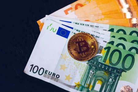 Golden bitcoin over Euro money. Bitcoin cryptocurrency. Crypto currency concept. Bitcoin with euro bills. Bitcoins stacked on euro banknotes.