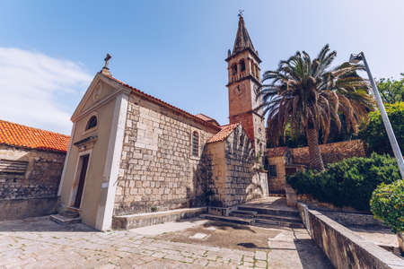 Church building and palm tree against sunny blue sky in Splitska village on Brac island, Croatia.