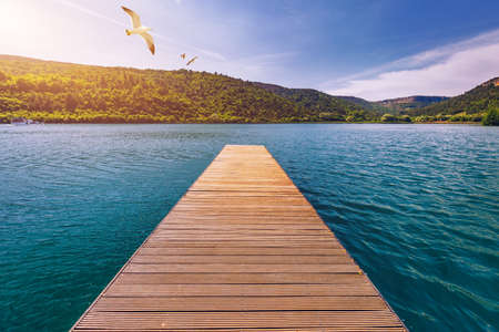 Idyllic view of the wooden pier in the lake with mountain scenery background. Wooden bridge on the lake. Long pier on lake and blue sky in summer.  Seagulls over pier. 写真素材