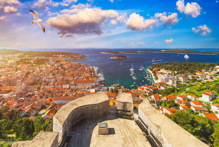 View at amazing archipelago in front of town Hvar, Croatia with seagulls flying over the city. Harbor of old Adriatic island town Hvar. Amazing Hvar city on Hvar island, Croatia.