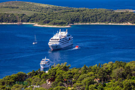 Luxury cruise boat with tropical island, panoramic view. Concept of long-distance cruise among the continents. Cruise Ship in the sea. Cruise ships close to island of Hvar, Croatia. 写真素材