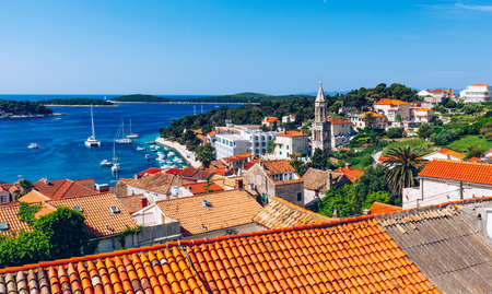 Panoramic view of Hvar town with lots of red roofs in Croatia. Hvar houses and roofs mediteranean town. Beautiful stacked houses in Hvar off the Dalmatian coast in Croatia. 写真素材