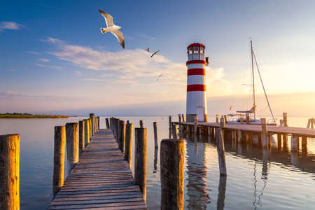 Lighthouse at Lake Neusiedl at sunset near Podersdorf with sea gulls flying around the lighthouse. Burgenland, Austria 写真素材