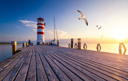 Lighthouse at Lake Neusiedl at sunset near Podersdorf with sea gulls flying around the lighthouse. Burgenland, Austria Stockfoto