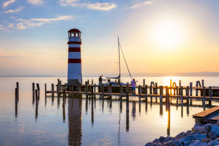 Lighthouse at Lake Neusiedl, Podersdorf am See, Burgenland, Austria. Lighthouse at sunset in Austria. Wooden pier with lighthouse in Podersdorf on lake Neusiedl in Austria. 写真素材