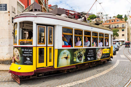 Lisbon, Portugal - June 8, 2018: Famous tram 28 full of tourists in Lisbon, Alfama district, Portugal in a summer day. Colorful tram through the historical streets of Lisbon, Portugal.