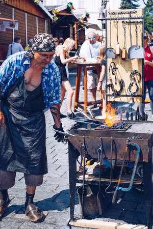 Prague, Czech Republic - May 26, 2018: Blacksmith works with metal close to open fire in Prague, Czech Republic.