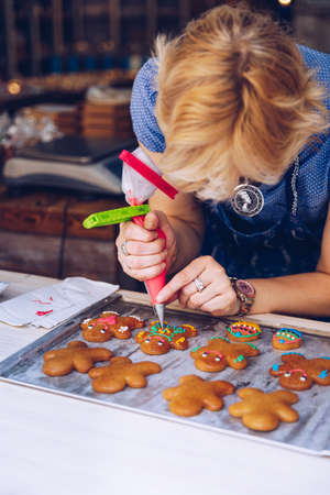 Unrecognizable women confectioner hand decorating a gingerman with a pastry bag, drawing a smile, making it cute, fun and delicious. Woman making ginger bread cookies in the kitchen. Редакционное