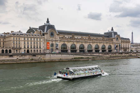 Paris, France - July 5, 2018: Musee dOrsay from the Seine River in Paris on an overcast day. Orsay museum (Musee d'Orsay) in Paris with Eiffel tower in the background, Paris, France.