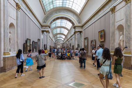 Paris, France - July 6, 2018: Many people appreciate paintings and sculptures in the Louvre Museum in Paris, France. The Louvre is the worlds largest museum and a historic monument in Paris, France.