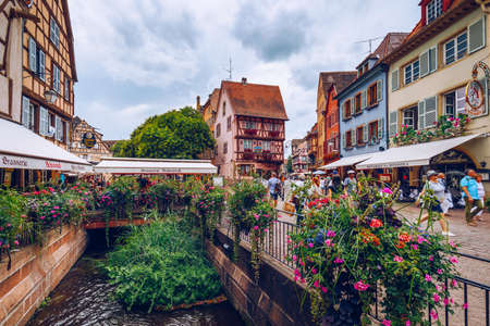 Colmar, France - July 27, 2018: Old town of Colmar, Alsace, France. View with colorful buildings, canal and flowers. Colmar, France. Petite Venice, water canal and traditional half timbered houses. Publikacyjne