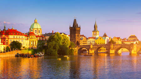 Malerischer Blick auf die Altstadt-Pierarchitektur und die Karlsbrücke über die Moldau in Prag, Tschechien. Prager ikonenhafte Karlsbrücke (Karluv Most) und Altstädter Brückenturm bei Sonnenuntergang, Tschechien.