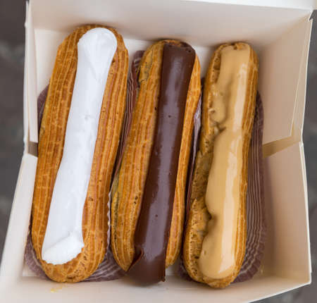 Colorful Eclairs In The Box. Eclairs Laying Inside White Boxes. Eclair Cakes With Scalded Carmel And Coffee Butter Cream. Фото со стока