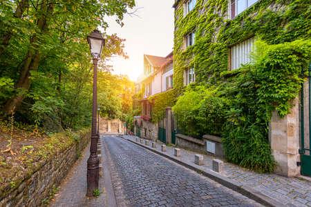 Montmartre district of Paris. Houses on narrow road in Montmartre district of Paris. View of cozy street in quarter Montmartre in Paris, France. Architecture and landmarks of Paris. Postcard of Paris.